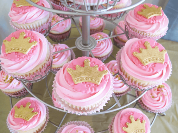 Pink cupcakes with pink frosting on a tiered cupcake stand. Each is topped with pink circles and gold crowns.