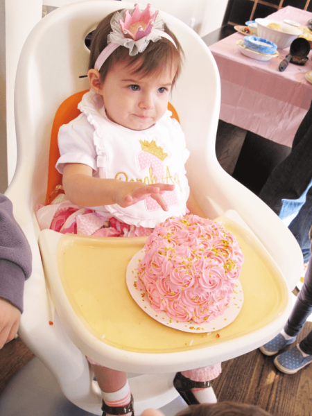 little girl with a pink crown in front fo a pink and gold smash cake.