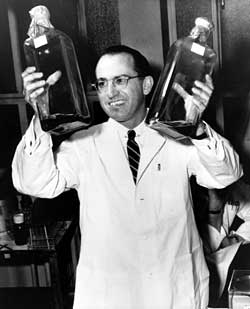 Jonal Salk--inventor of the polio vaccine--holding two bottles of vaccine solution.