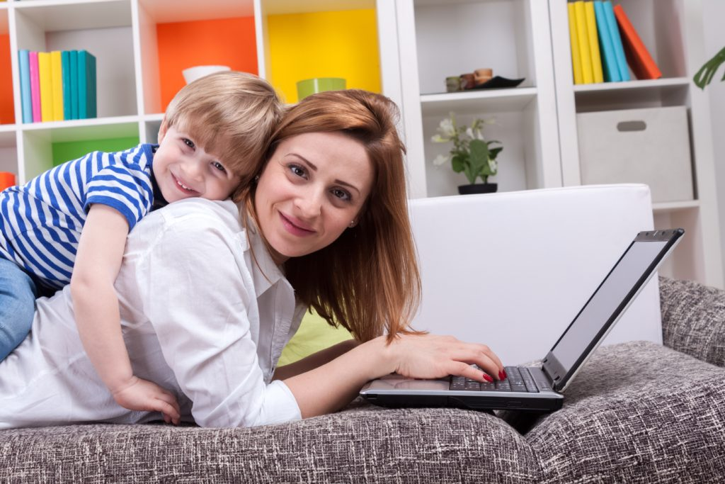 Woman with child lie on sofa and using computer
