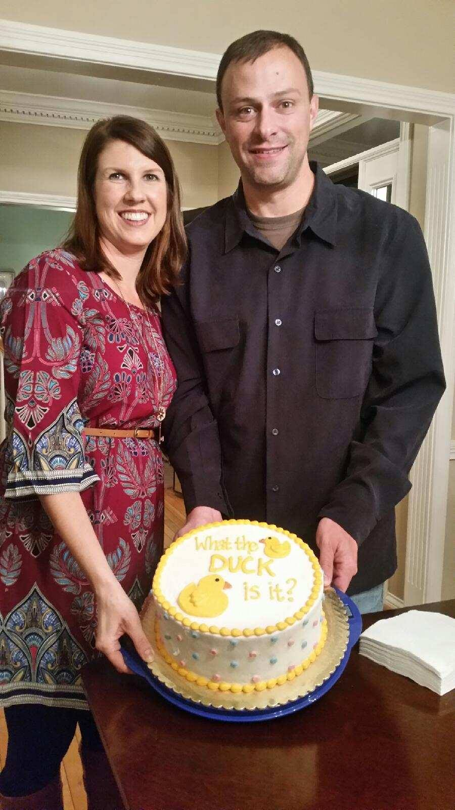 Man and woman stand holding a cake with a duck on it.