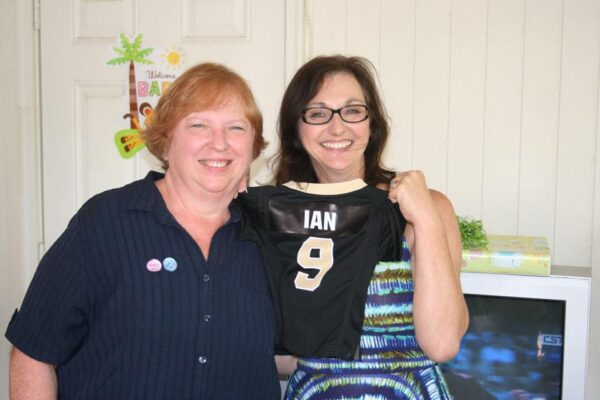two grandmothers stand holding a tiny football jersey with a name on the back