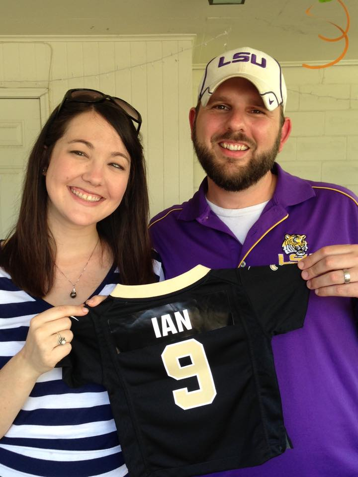 couple stands holding tiny Saints football jersey with name on the back