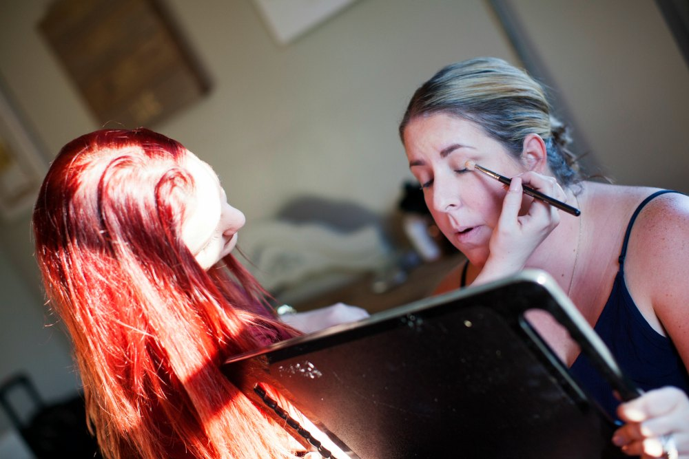 red headed woman applies eye makeup to another woman with eyes closed