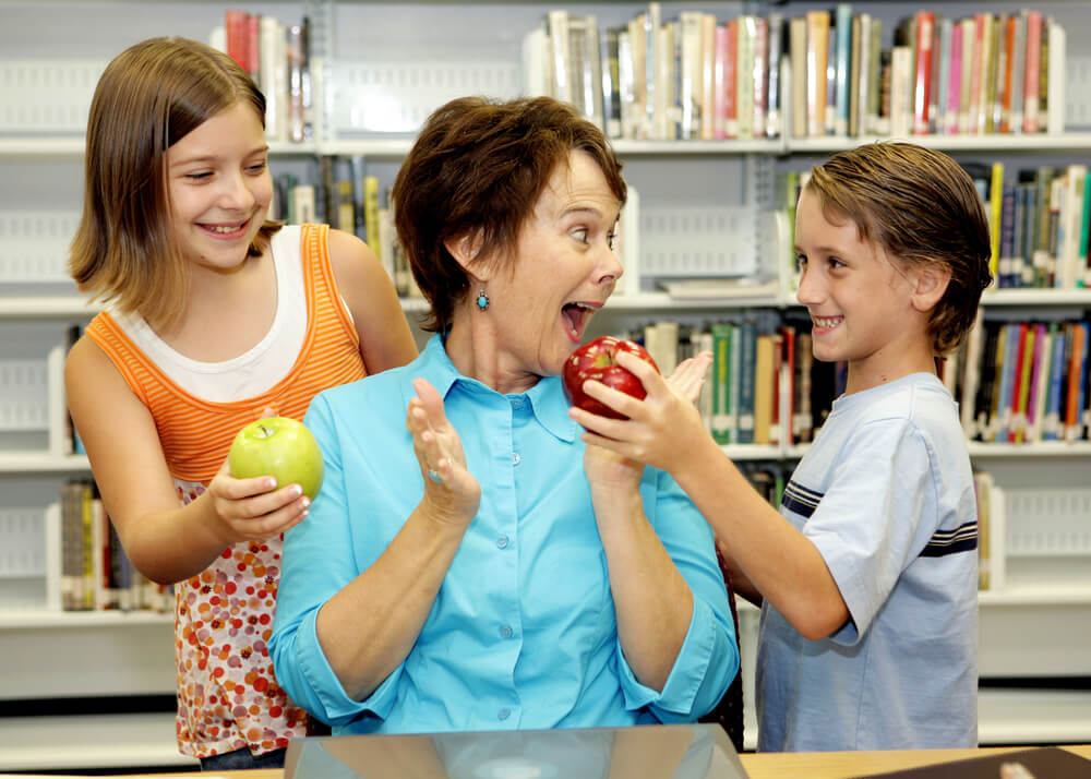 teacher in a blue shirt at her desk. Two children are bringing her apples and she looks happy. There are books on the shelf behind her.