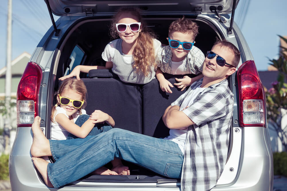 a dad and three kids sitting in the trunk area of an SUV